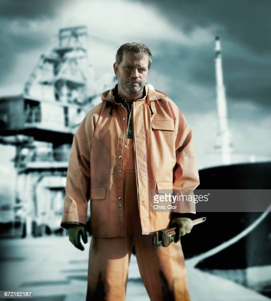 serious caucasian worker holding wrench on oil rig - dock worker stock photos and pictures