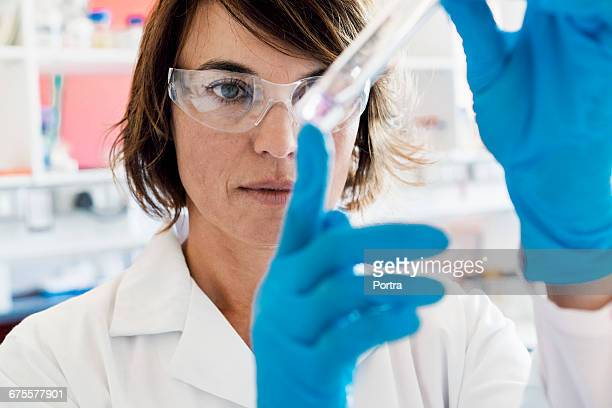Serious chemist analyzing chemical in test tube
