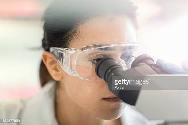 serious chemist using microscope at laboratory - microscope stock pictures, royalty-free photos & images