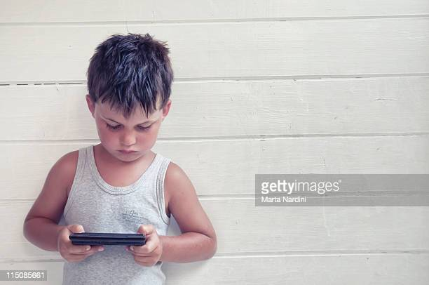 serious child plaing at portable videogames - handheld video game stock pictures, royalty-free photos & images
