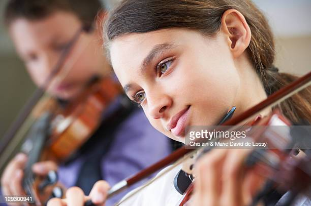 serious children playing violin - violin family stock photos and pictures