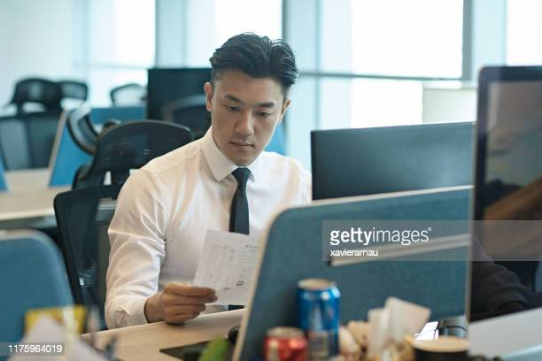 オフィスデスクで文書を読む深刻な中国人ビジネスマン - デスクトップ型パソコン ストックフォトと画像