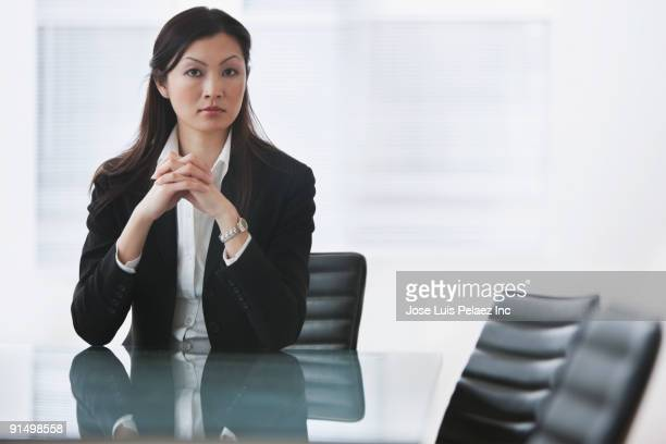 Serious Chinese businesswoman sitting at conference table