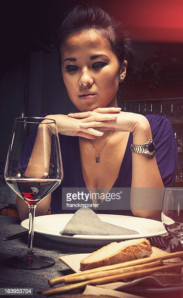 Serious Chinese girl waiting at restaurant