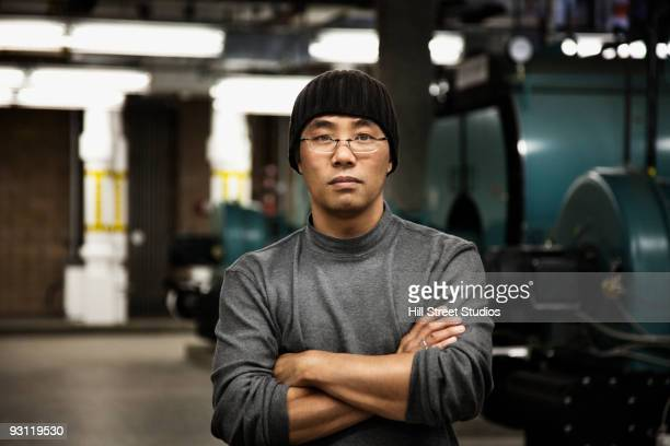 Serious Chinese man with arms crossed in industrial plant