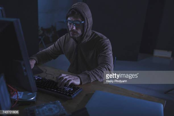serious computer hacker wearing hooded shirt using desktop computer at table in abandoned room - con man stock photos and pictures