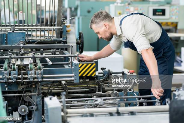 serious concentrated bearded repairman in overall examining industrial machine and adjusting it before work - mechanical engineering stock pictures, royalty-free photos & images