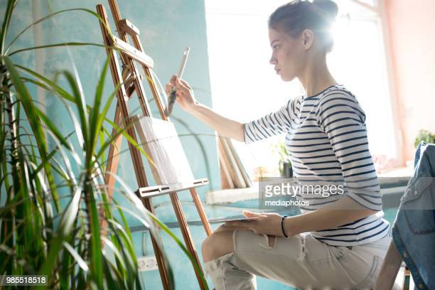 Serious concentrated creative painter sitting at easel and applying paint with brush on canvas in own workshop