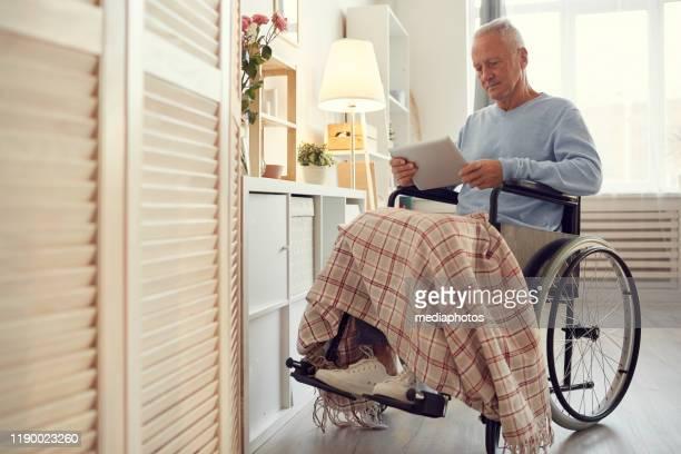 車椅子に座り、タブレットでオンライン記事を読む麻痺した足を持つ深刻な集中障害者シニア男性 - 麻痺 ストックフォトと画像