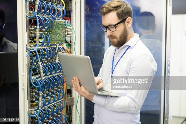 Serious concentrated handsome male technician typing on laptop while correcting data taken from supercomputer in server room of mining farm