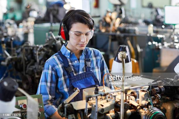 serious concentrated lady in protective goggles wearing ear protectors standing at lathe and operating machine while processing spare parts for wristwatch - ear protection stock pictures, royalty-free photos & images