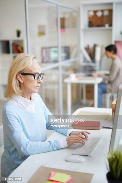 Serious concentrated mature lady in blue sweater sitting at desk and working on desktop computer in modern office
