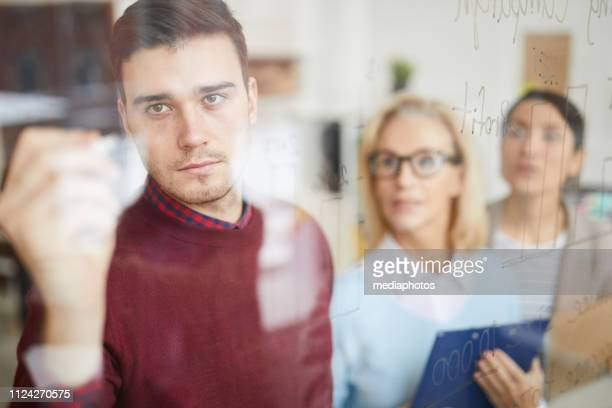 Serious concentrated young male marketer in sweater writing data on board while explaining strategy to colleagues in modern office