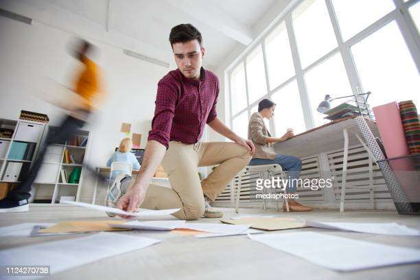 Serious concentrated young manager with stubble wearing checkered shirt standing on one knees and putting papers on floor while analyzing information in office