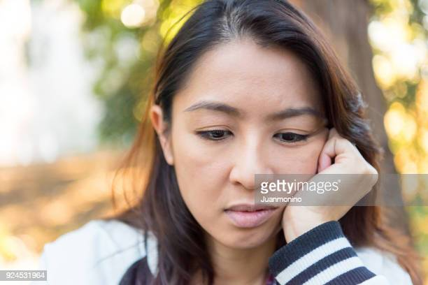serious concerned asian woman looking down - mongolian women stock photos and pictures