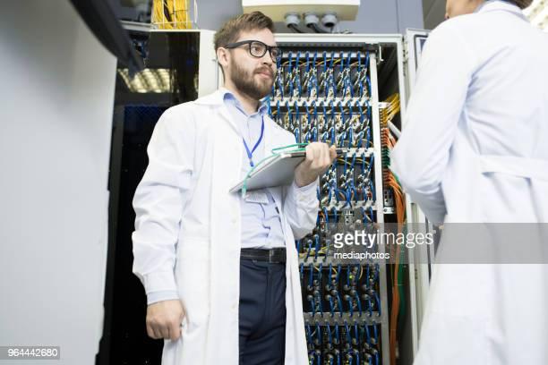 Ernsthafte zuversichtlich Datacenter-Spezialist mit Laptop Gespräch mit professionellen es Ingenieur während sie Planung Verbesserung des Servers auf Bergbau farm