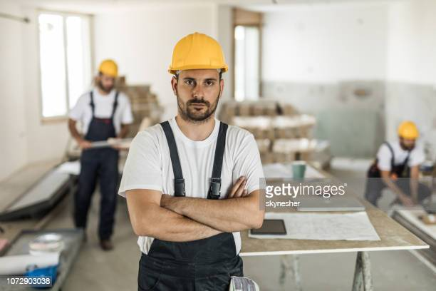 Serious construction worker with crossed arms looking at camera.