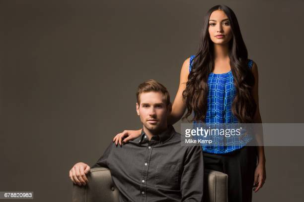Serious couple posing with armchair