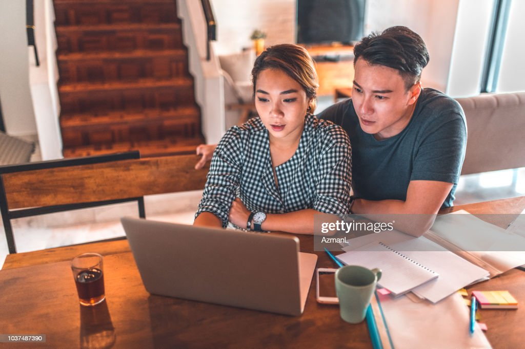Serious couple using laptop while sitting at home : Foto de stock