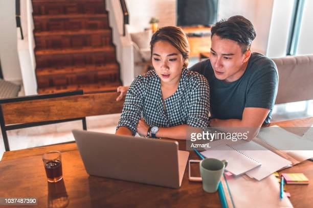 serious couple using laptop while sitting at home - coppia di giovani foto e immagini stock