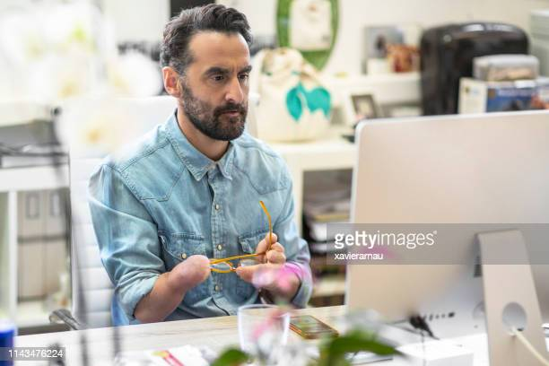 serious disabled businessman using computer - disabled stock pictures, royalty-free photos & images
