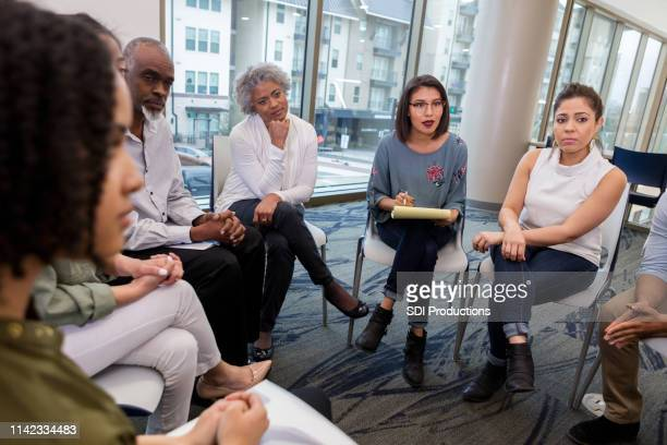 serious discussion during group therapy - mid adult stock pictures, royalty-free photos & images