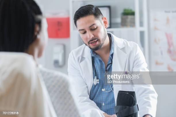 serious doctor helps female patient with orthopedic boot - coluna vertebral humana imagens e fotografias de stock
