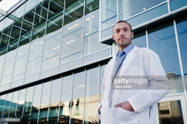 Serious doctor standing outdoors