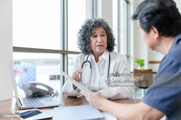 serious doctor talks with patient about a medical document - cardiologist stock pictures, royalty-free photos & images
