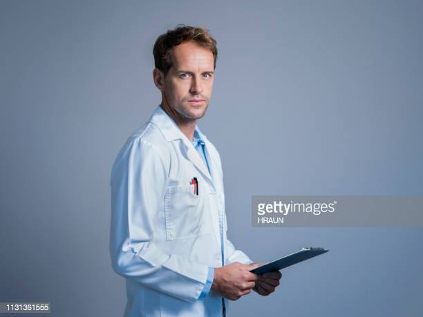 serious doctor with clipboard over gray background - three quarter length stock pictures, royalty-free photos & images