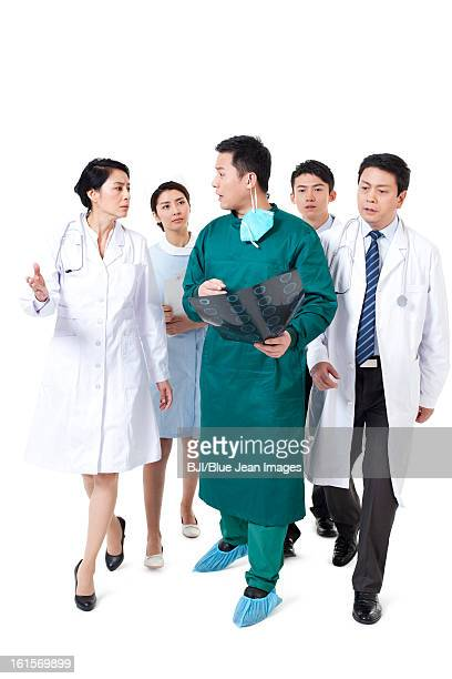 serious doctors and nurse with x-ray plate in hand walking and talking - shoe covers stock pictures, royalty-free photos & images