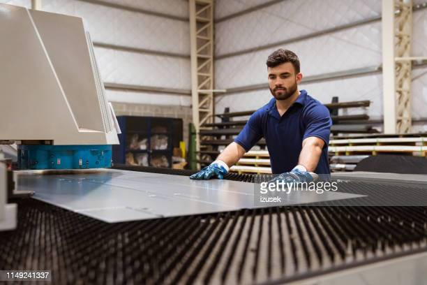 serious engineer adjusting metal on puller machine - sheet metal stock pictures, royalty-free photos & images