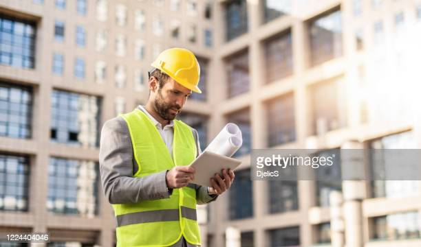 serious engineer using digital tablet. - real estate developer stock pictures, royalty-free photos & images