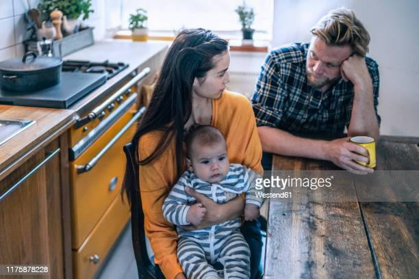 serious family with baby sitting at kitchen table at home - beide elternteile stock-fotos und bilder