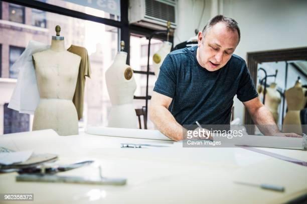 serious fashion designer working at table in design studio - デザイナー服 ストックフォトと画像