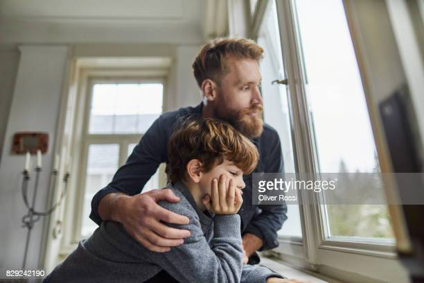 Serious father and son looking out of window