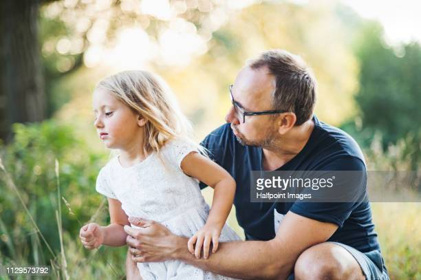 A serious father scolding a naughty toddler daughter outdoors in nature in summer.