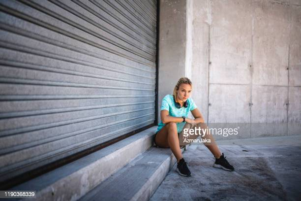 serious female athlete taking a rest in shade - roller shutter stock pictures, royalty-free photos & images