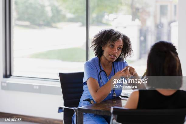 serious female doctor talks with patient - gynecologist stock pictures, royalty-free photos & images