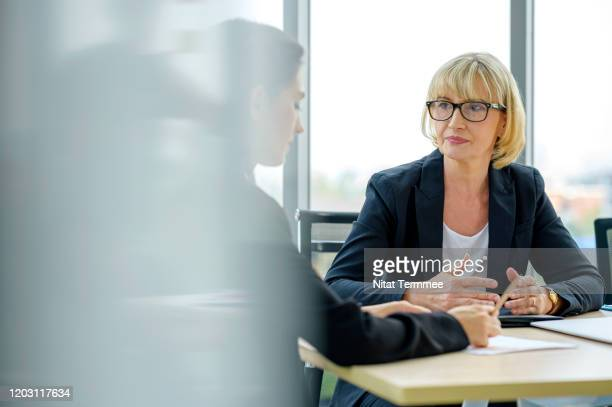 serious female financial advisor and client talking and discussing financial plan or investment plan. - vermögensberatung stock-fotos und bilder