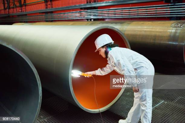 serious female inspector examining inner side of tube - female flasher stock pictures, royalty-free photos & images