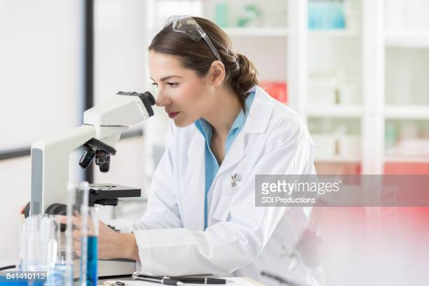 serious female lab intern studies microscopic image - microscope stock pictures, royalty-free photos & images