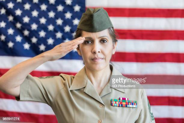 serious female military officer salutes american flag - saluting stock pictures, royalty-free photos & images