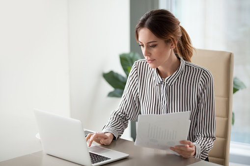 Serious focused businesswoman typing on laptop holding papers preparing report 1129638600