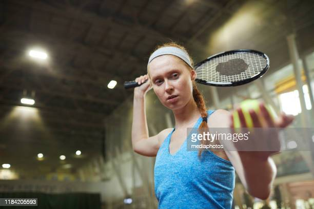 serieuze gerichte vrouwelijke professionele tennisser in blauw shirt en hoofdband staande op indoor court en serveren bal tijdens het starten van de wedstrijd - court hearing stockfoto's en -beelden