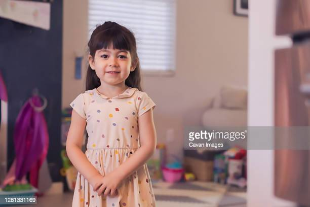 serious four year old girl in polka dot dress looking at camera. - sonntag stock-fotos und bilder