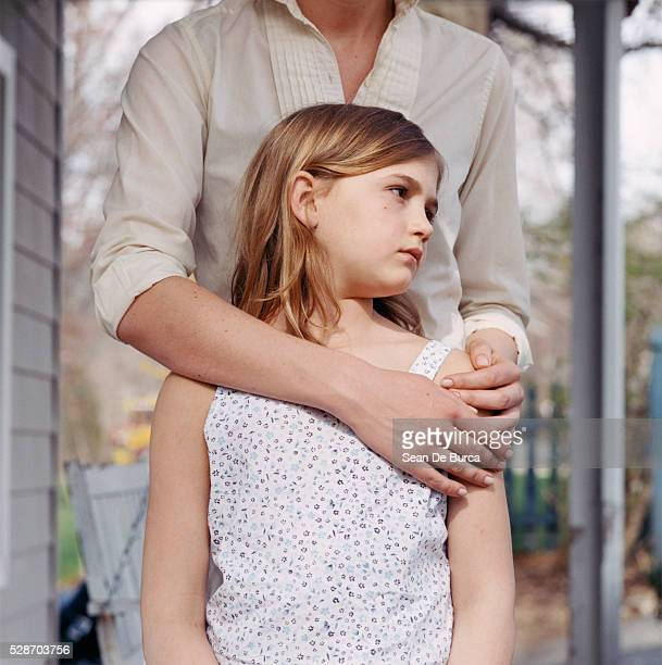 Serious Girl with Mother's Arm Around Her