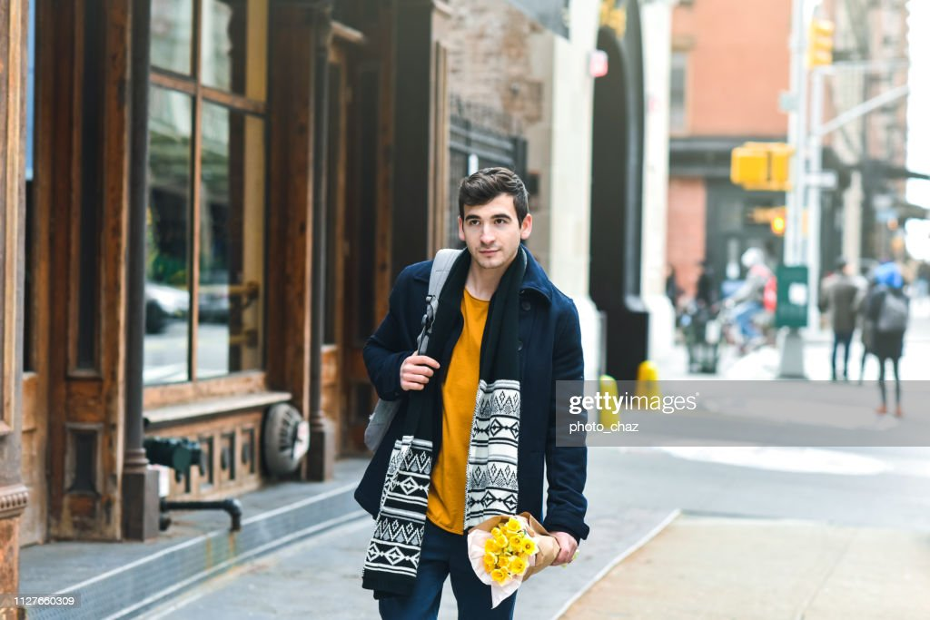 Serious Guy Walking with Flowers : Stock Photo