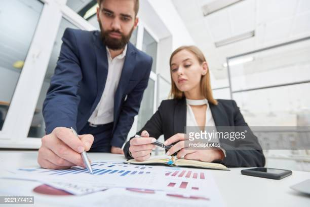 serious handsome assistant showing business papers - risk stock pictures, royalty-free photos & images