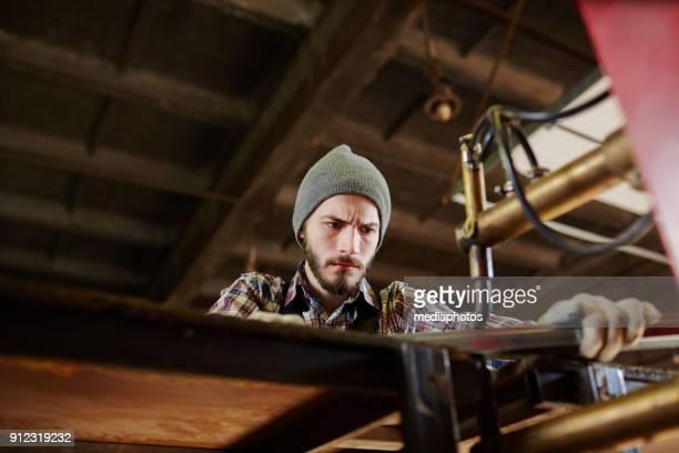 Serious handsome craftsman making metal detail